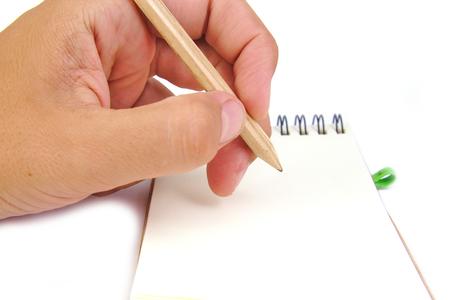 연필로 손을 흰색 배경에 노트북에 메모를 스톡 콘텐츠
