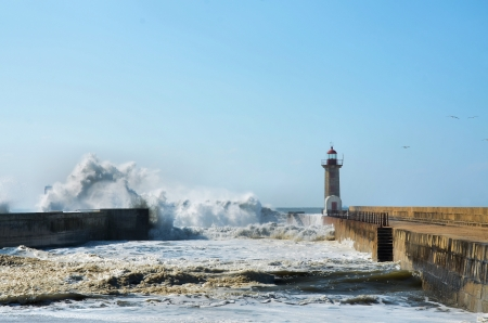 Strong waves hitting the breakwaters and the lighthouses photo