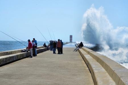 despite: Fishermen on the pier despite the strong waves