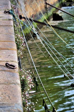 iron hoops: Ropes for mooring boats in the riverside Stock Photo
