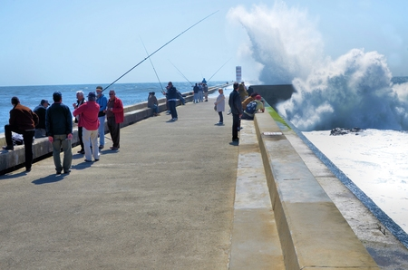 despite: Fishermen on the pier despite the strong waves