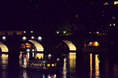 Historic bridge over the Vltava river in the city of Prague at night