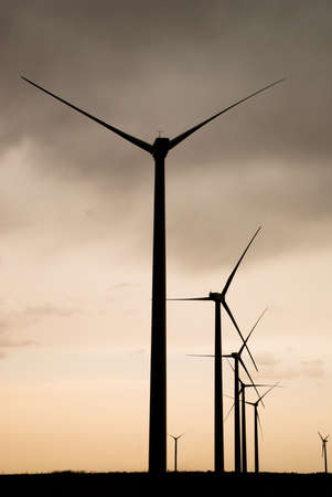 wind mills: silhouettes of wind mills with a cloudy background Stock Photo