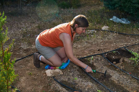 Woman working in her garden preparing the land for planting Banque d'images - 150990765