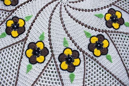 White and brown crochet piece with yellow and brow flower with two green leaves next each one