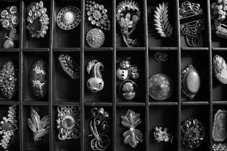 A lot of differents broochs and pins displayed inside a black box. There are golden pins, gemstones, various formats and colors. Silver and iron can be found too. [Black and White version]
