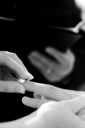 Black And White Image Of Rings Being Exchanged By A Bride And Groom During Wedding Matrimony photo