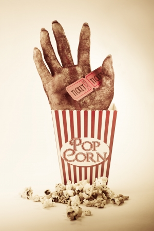 Frightening Picture Of A Creepy Sawn Off Hand Poking Out Of A Striped Pop Corn Box Holding Two Cinema Movie Tickets In A Horror Movie Conceptual photo