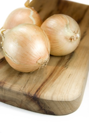 Unpeeled Onions Sit On An Isolated Chopping Board photo