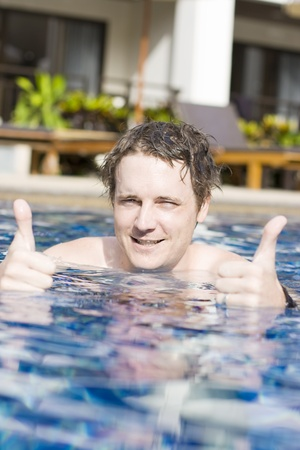 Portrait Of Smiling Young Man With Thumbs Up In Swimming Pool Stock Photo - 11589807