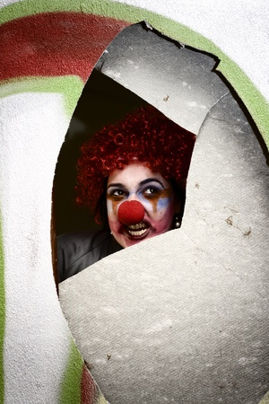 The Creepy Clown From Childhood Terrors Looks Through A Hole In The Wall With A Chilling Stare …. Waiting And Watching photo