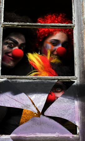 Dark Carnival Clowns Looking Sinister And Scary Peer Through A Haunted House Window At A Chilling Halloween Party Stock Photo - 11590822
