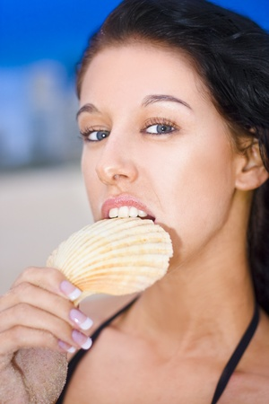 Attractive Young Woman With Black Hair And Blue Eyes Holds Pretty Seashell In Her Mouth With A Bright And Glowing Expression Stock Photo - 11590198