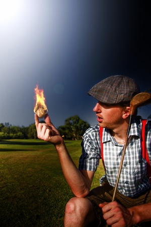 Golfer Sitting On A Golf Course Looks Shocked And Stunned At A Golf Ball In His Hands Burning Bright In A Blaze Of Fire And Flames photo