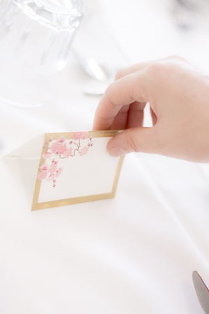 Persons Hand Places A Guest Name Tag On A Venue Table During A Wedding Reception Setup Stock Photo - 11584114