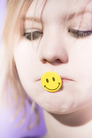 Sad And Depressed Woman With A Smile Badge In Her Mouth Puts On A Happy Face Stock Photo - 11590178