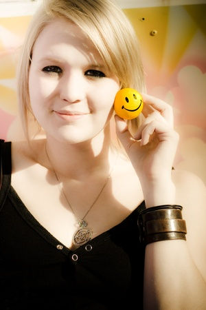 Soft Portrait Of A Beautiful Young Blond Woman Sitting At A Fair Holding Up A Happy Smiley Face Emoticon Ball In A Positive Expression Of Joy And Happiness Stock Photo - 11589810