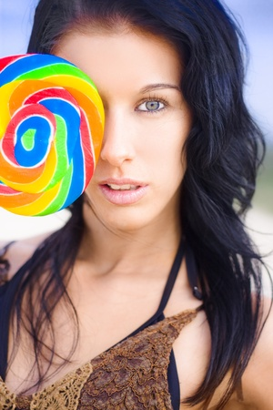 Beautiful Young Woman With Black Hair And Pretty Face Holding Lollipop In Front Of One Of Her Eyes With A Flirtatious Expression Stock Photo - 11584697