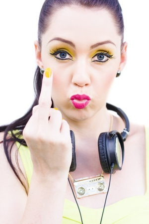 In A Offensive Anti Social Gesture Of Bad Manners A Rebellious Punk Rock Girl Wearing Headphones Solutes Her Middle Finger In A Rude DJ Or Angry Music Concept Stock Photo - 11584175