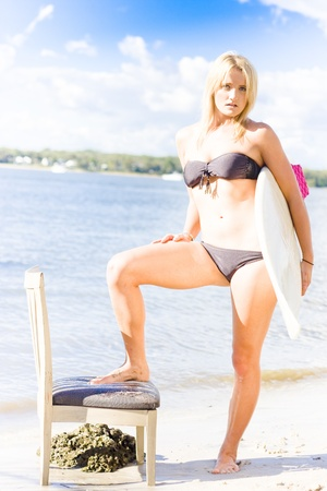 Good Looking Blonde Lady Wearing Bikini Modeling A Surfboard With Seat At A Rocky Ocean Location In A Surf Model Concept photo
