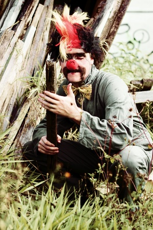 Bashful The Clown Holds A Block Of Wood While Kneeling Down Outdoors During A Malicious Portrait Of Evil Intent photo