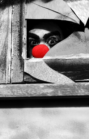 Peeking Through A Broken Window Pane A Creepy Ghoulish Clown Watches The Halloween Peek A Boo Stock Photo - 11584707