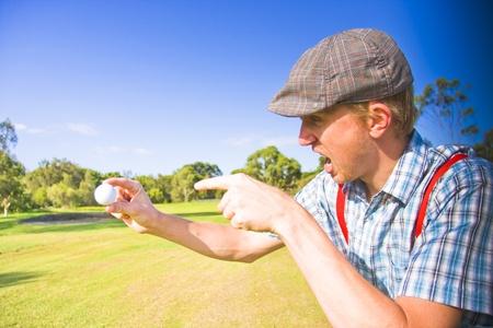 Golf enojado ve a un hombre Deportes gritando hacia fuera en un ataque de rabia En un campo de golf mientras apunta a su pelota de golf despu�s de un juego de golf sin �xito photo