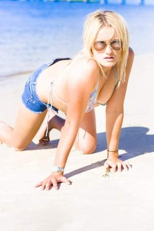 Gorgeous Young Blonde Summer Girl Wearing Mirror Sun Shades While Modeling On Sand In A Bright Outdoor Portrait In The Sunshine, Copyspace On Sand Below Model photo