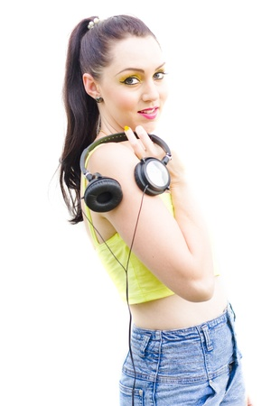 Isolated Studio Portrait Of A Beautiful Young Brunette Girl Holding A Set Of Earphones Or Head Phones Standing In A Cool 80s Fashion Sound Portrait, White Background photo