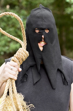Black Hooded Medieval Hangman Stands With An Look Of Anger And Hatred With Rope Noose At Outdoor Gallows photo