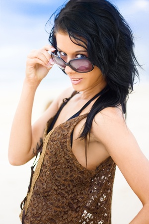 Young Woman Wearing Stylish Bikini And Cover-up With Confident And Playful Expression Looking Over Her Sunglasses With Blue Sky And Beach Background photo