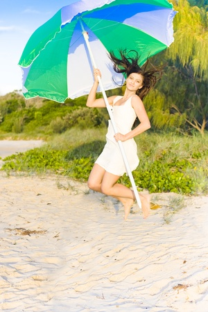 Healthy Fit And Young Woman Jumping Outdoors At A Beach Location With A Umbrella In A Fun And Happiness Concept photo