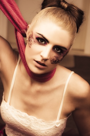 Image Of A Beautiful Glamour Fashion Model With Fine Art Lace Makeup Pulling Neck Scarf Tight In A Clothing Control Or Fashion Victim Conceptual photo