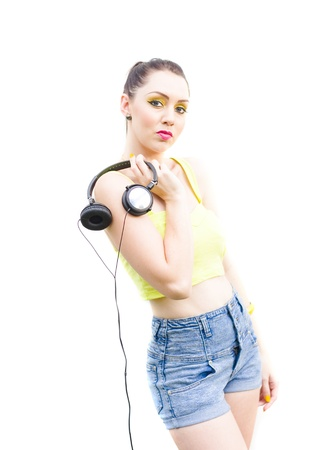 White Background Portrait Of An Attractive Retro Female Posing With Attitude And Stereo Sound Earphones In A Eighties Streetwear Musical Conceptual photo