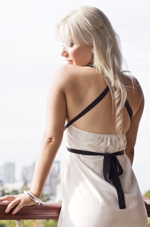 Rear half body portrait of young blond woman in stylish dress with city in background and white sky. photo