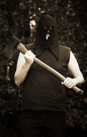 Hooded Medieval Executioner With Axe Trees In Background Stock Photo - 11589815