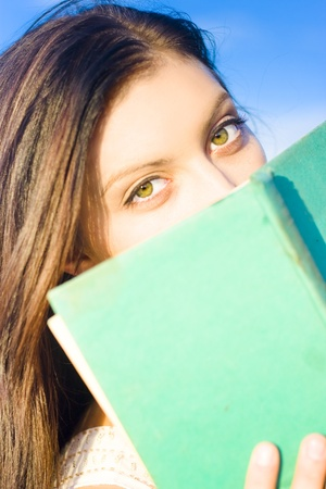 Face Of A Young Beautiful And Attractive Girl Holding A Book In A Fact Finding Study Of Information Discovery In Wisdom And Knowledge Stock Photo - 11584592