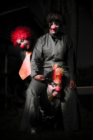 Three Clowns With Curly Wigs In Playful Position With Dark Background Stock Photo - 11590167