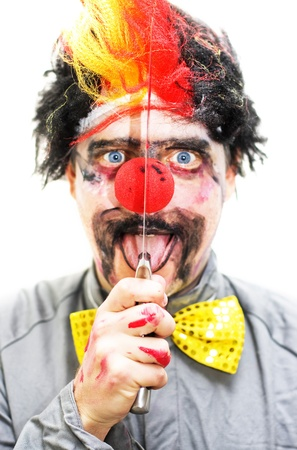Sinister Clown Holds Up A Knife Vertical To His Face While Opening His Mouth In A Creepy Isolated Expression photo
