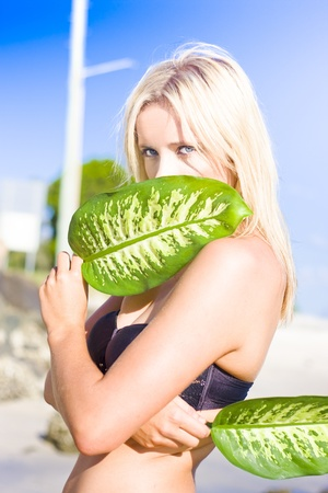 Young Blonde Woman With Blue Eyes Holding Large Tropical Leaf In Front Of Her Face With An Alluring Expression Stock Photo - 11584664