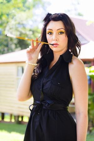 Glamorous And Fashionable Woman Thinking While Smoking A Lit And Smoldering Cigarette Through A Vintage Holder Outdoors In A Vintage Fashion Glamour Portrait photo