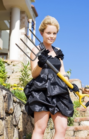 Looking Armed And Dangerous A Attractive Blonde Lady Wearing A Formal Dress Holds A Pitch Fork At Home In Her Front Garden Stock Photo - 11589937