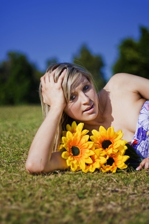 Summer Sun Flowers Woman Lays With Bright Yellow Sunflowers\ In Her Arms In Summers Sunny Sunshine During Sunlight