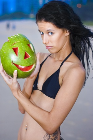 Beautiful Blue Eyed Bikini Woman With Joking And Teasing Expression Holding A Carved Happy Face Watermelon As If She Finds The Situation To Be Humorous Stock Photo - 11590210