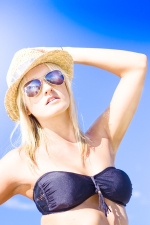 Half Body Portrait Of A Beautiful Young Blond Woman Wearing Bikini On Summer Vacation Standing Holding Hat Wearing Sun Shades Against Clear Blue Sky Stock Photo - 11584813