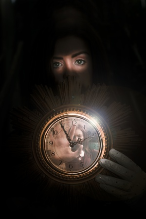 Clock Held By Young Woman Shadowed In Black With Another Woman Stuck Inside The Glass Face Of The Timepiece In A Lost In Time Concept photo