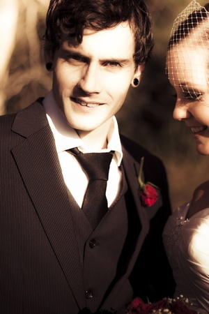 Sepia Tone Photo Of A Handsome And Vintage Young Groom At His Wedding Posed With His Smiling Bride Looking At The Camera With Searing Gaze Stock Photo - 11589869