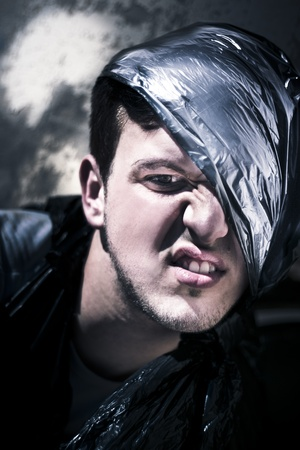 Angry Homeless Man Wearing A Bin Bag On His Head Expresses Anger In A Face Portrait While Living In Garbage On The Street In A Crazy About Garbage Concept photo