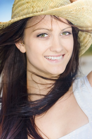 Closeup On The Beautiful Smiling Face Of A Happy Country Woman Wearing A Cowgirl Hat photo