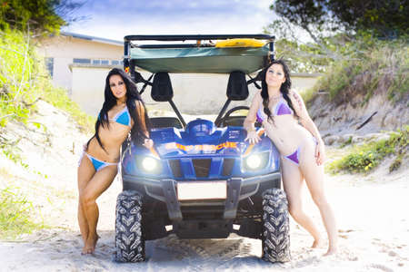 Two Sexy Female Beach Babes Pose Beside A Surf Rescue Dune Buggy 4x4 Car On A Sandy Beach In A Lifeguard Sea Patrol Concept photo
